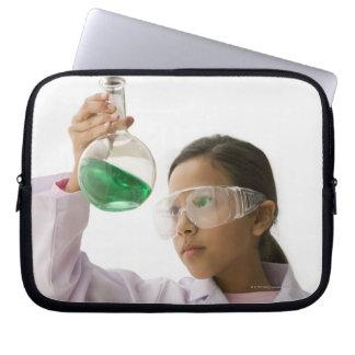 Hispanic girl looking at liquid in beaker laptop sleeve
