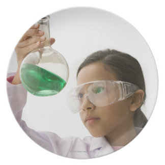 Hispanic girl looking at liquid in beaker plate