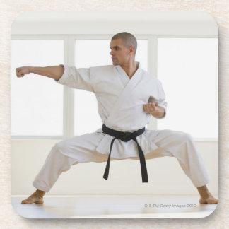 Hispanic male karate black belt in fighting coasters