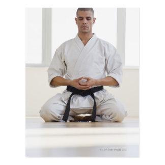 Hispanic male karate black belt meditating postcard