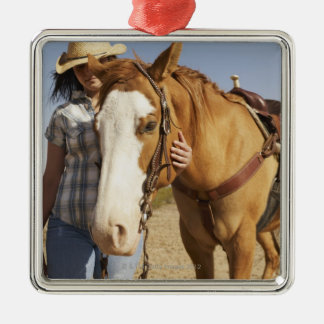Hispanic woman standing next to horse christmas ornament