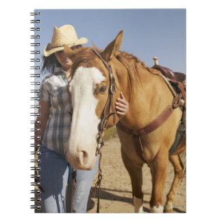 Hispanic woman standing next to horse notebook