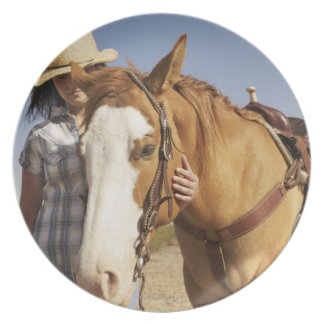Hispanic woman standing next to horse plate