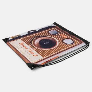 holding retro old manual camera drawstring bag