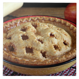 Home baked apple pie on cooling rack with apple tile