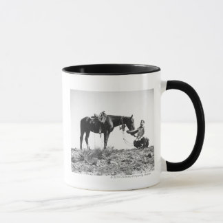 Horse eating from a cowboy's hat. mug