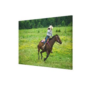 Horseback rider galloping in rural pasture canvas print