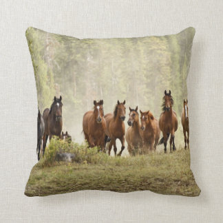Horses cresting small hill during roundup throw pillow
