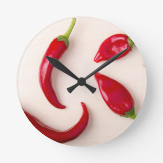 Hot red chili peppers on a light wooden board wallclocks