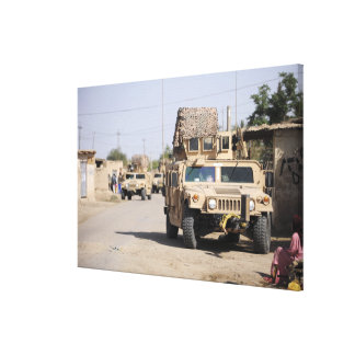 Humvee's conduct security during a patrol stretched canvas prints