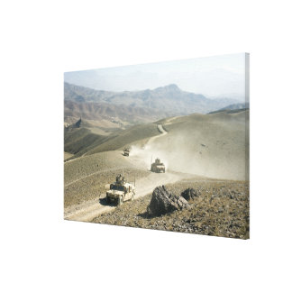 Humvees traverse rugged mountain roads canvas print