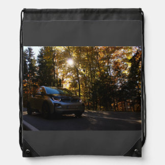 Hybrid car on a highway drawstring bag