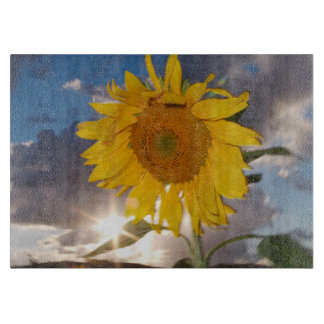 Hybrid sunflower blowing in the wind at dusk cutting board