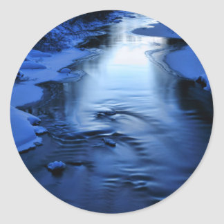 Icy and snowy river with winter blue round sticker