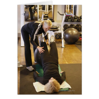 Instructor helps senior client with stretches card