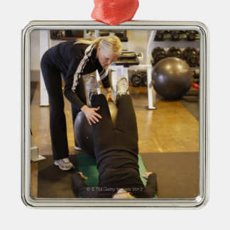 Instructor helps senior client with stretches Silver-Colored square decoration