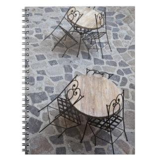 Italy, Sardinia, Castelsardo. Cafe tables. Notebooks
