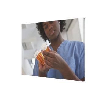 Jamaican female nurse checking pill bottles canvas prints