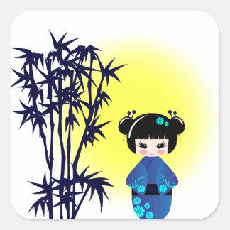 Japanese kokeshi doll at bamboo during sunrise square sticker