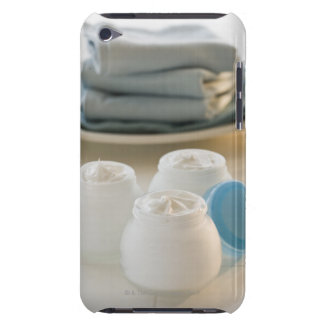Jars of moisturizing creams and stack of towels iPod Case-Mate case