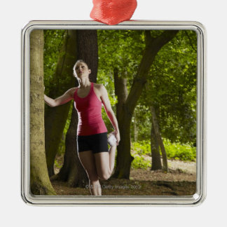 Jogger stretching in forest ornaments