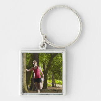 Jogger stretching in forest key ring