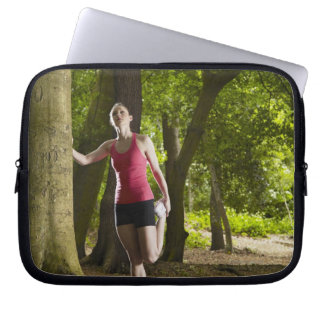 Jogger stretching in forest laptop sleeve