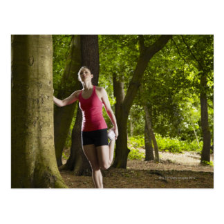 Jogger stretching in forest postcard