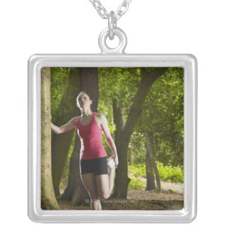 Jogger stretching in forest silver plated necklace