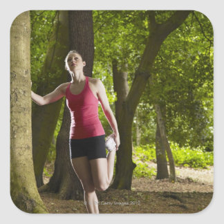 Jogger stretching in forest square sticker