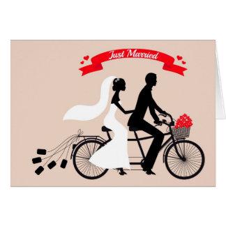 Just married, bride and groom on wedding bicycle greeting card