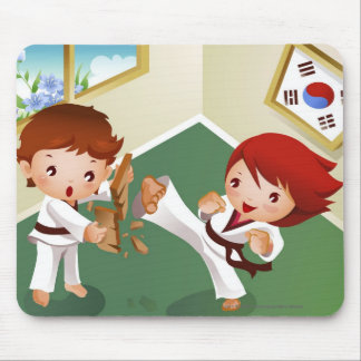 Karate boy holding wood with another breaking it mouse mat