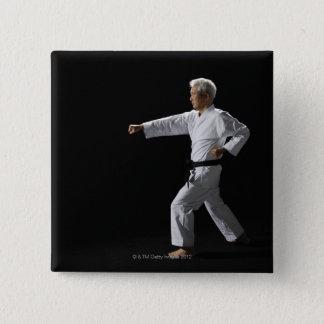 Karate master demonstrating, studio shot 15 cm square badge