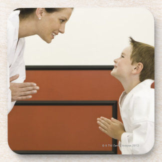 Karate teacher and boy (4-5 years) bowing to beverage coasters