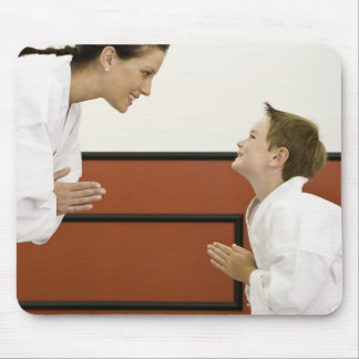 Karate teacher and boy 4-5 years bowing to mouse pads