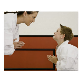 Karate teacher and boy (4-5 years) bowing to poster