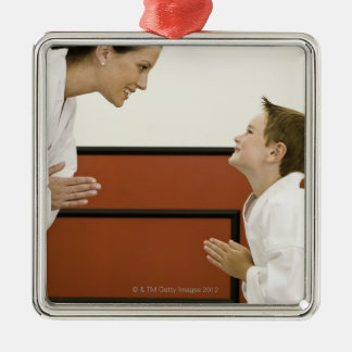 Karate teacher and boy (4-5 years) bowing to Silver-Colored square decoration