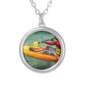 Kayaker paddling in clear water pendants