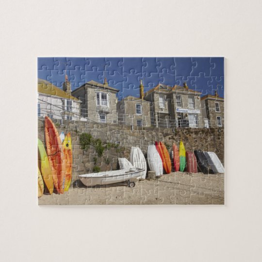 Kayaks and dinghies stacked against seawall at jigsaw