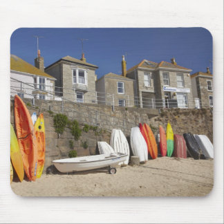 Kayaks and dinghies stacked against seawall at mouse mat