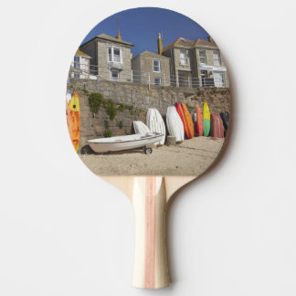 Kayaks and dinghies stacked against seawall at ping pong paddle