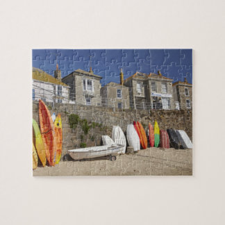 Kayaks and dinghies stacked against seawall at puzzle
