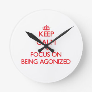 Keep calm and focus on BEING AGONIZED Round Wallclocks