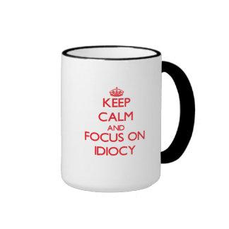 Keep Calm and focus on Idiocy Coffee Mugs