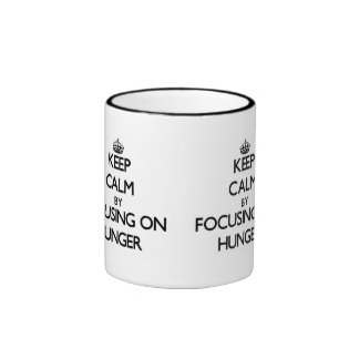 Keep Calm by focusing on Hunger Coffee Mugs