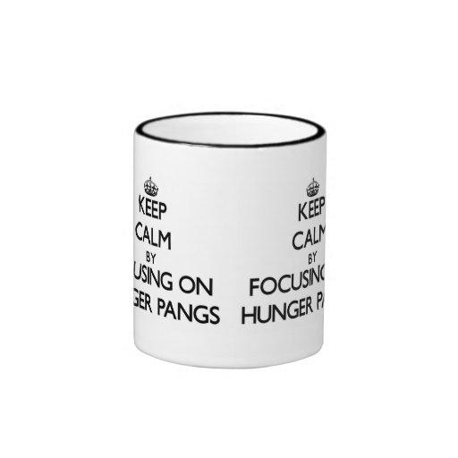 Keep Calm by focusing on Hunger Pangs Coffee Mugs