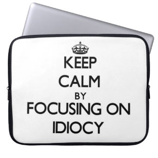 Keep Calm by focusing on Idiocy Laptop Sleeves