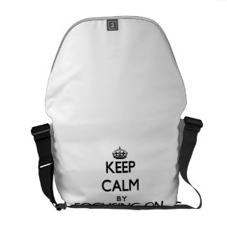 Keep Calm by focusing on Idiocy Courier Bags