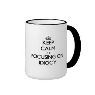 Keep Calm by focusing on Idiocy Mugs