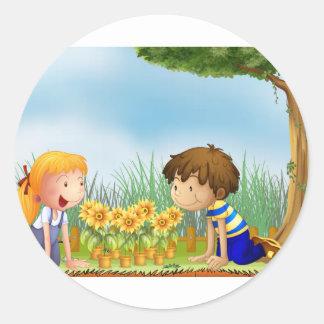 Kids watching the pots of sunflower round sticker